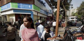 Pedestrians walk by a Standard Chartered Mumbai
