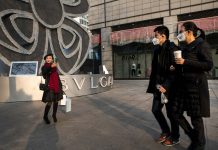 Pedestrians walk past a shopper taking a selfie; China's generation z;