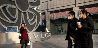 Pedestrians walk past a shopper taking a selfie; China's generation z;
