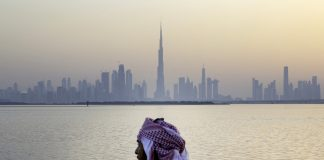 An Emirati man looks out from the Dubai Creek Habour Development towards the Burj Khalifa tower, center, and other skyscrapers in Dubai, United Arab Emirates, UAE