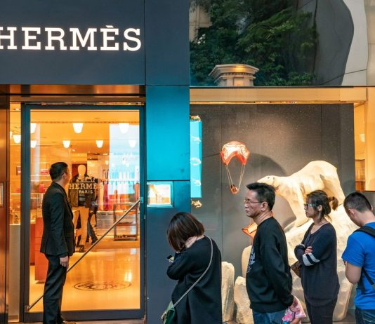 Shoppers wait in line outside a Hermes International store