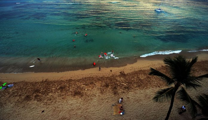 Tourists enjoy at the Waikiki beach vacation in Honolulu, Hawai.