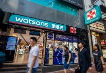 Pedestrians walk past a Watsons store