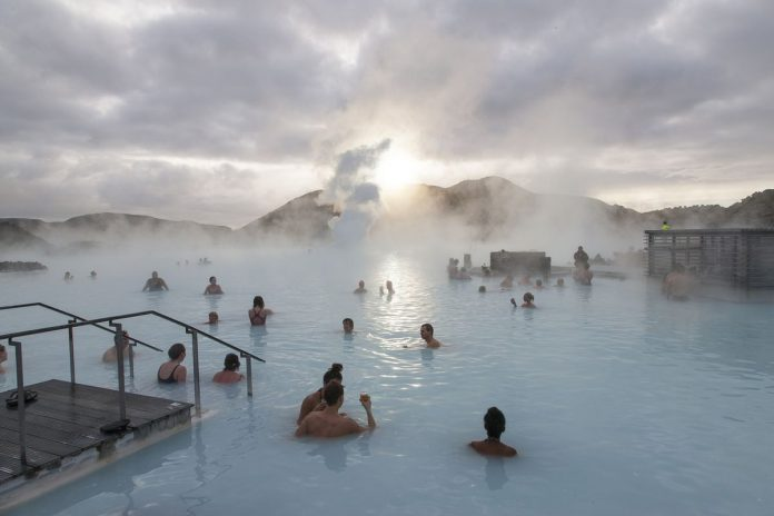 Tourists bathe in the Blue Lagoon geothermal spa as steam rises in Grindavik, Iceland.