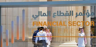 Saudi participants pass by a sign of the Financial Sector Conference held in Riyadh, on April 24, 2019.