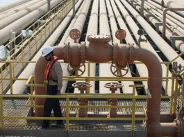 An employee inspects pipes used for landing and unloading crude and refined oil at the North Pier Terminal, operated by Saudi Aramco